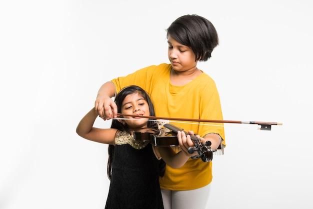 흰색 배경 위에 격리된 바이올린을 연주하는 귀여운 인도 또는 아시아 소녀