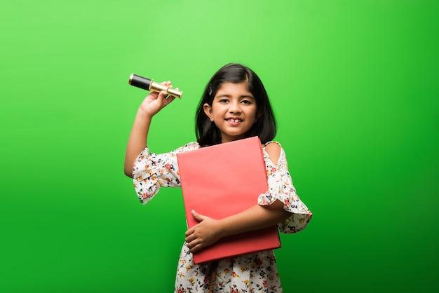 Милая маленькая индийская или азиатская девочка, использующая растяжной телескоп и смотрящая в небо, хочет быть ученым. стоя изолированные на белом или зеленом фоне классной доски