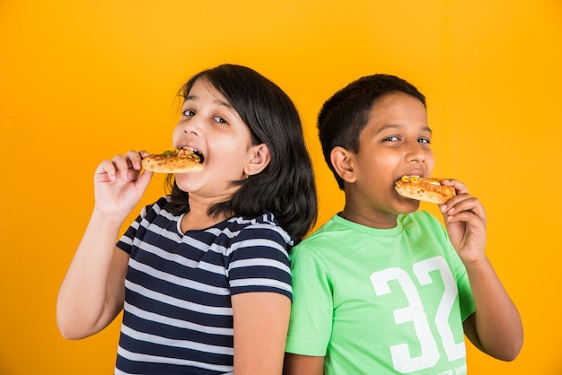 プレートまたはボックスでおいしいハンバーガー、サンドイッチまたはピザを食べるかわいい小さなインドまたはアジアの子供たち。青または黄色の背景の上に孤立して立っています。