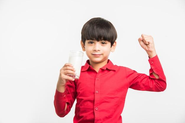 白い背景の上に隔離、ミルクでいっぱいのグラスを保持または飲んでかわいい小さなインドまたはアジアの遊び心のある男の子
