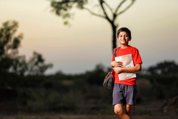 Милый маленький индийский школьник с записной книжкой и сумкой