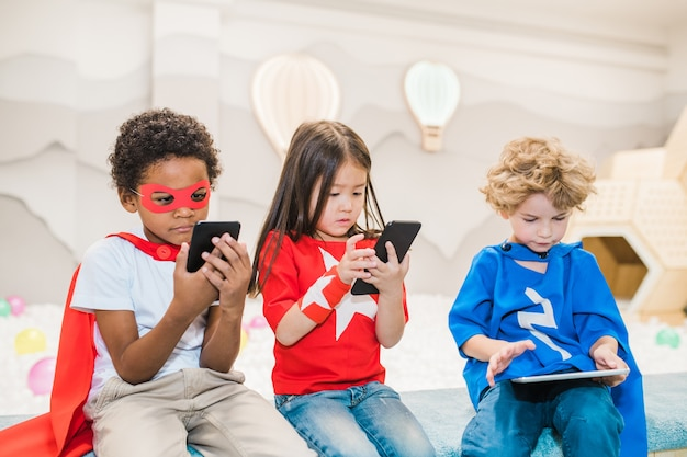 Симпатичные маленькие межкультурные друзья с мобильными гаджетами играют в игры или смотрят мультфильмы в развлекательном центре