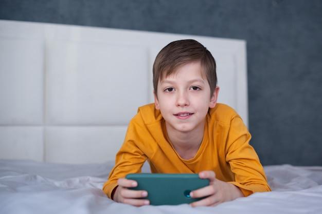 スマートフォンに焦点を当てたベッドに横たわっているかわいい男の子