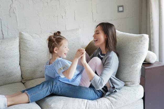 ソファの上で母親と遊んで笑っているかわいい小さな子供の娘、リビングルームで一緒に余暇を楽しんでいる面白い小さな子供の女の子の絆を楽しんでリラックスしている幸せな母親。