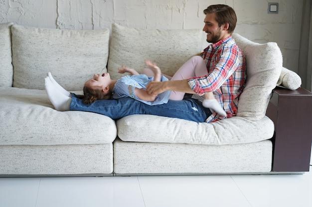 ソファでお父さんと遊んでくすぐり笑っているかわいい小さな子供の娘、リビングルームで一緒にレジャーを楽しんでいる面白い小さな子供の女の子の絆を楽しんでリラックスしている幸せな父。