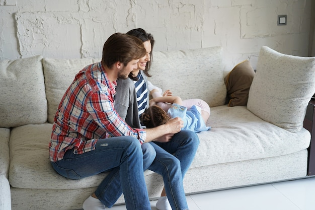 ソファで両親と遊んでくすぐり笑うかわいい小さな子供の娘、幸せな父と母は、リビングルームで一緒にレジャーを楽しんで面白い小さな子供の女の子の絆を楽しんでリラックスしています。