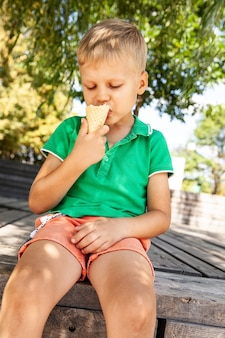 Милый маленький ребенок ест мороженое в парке