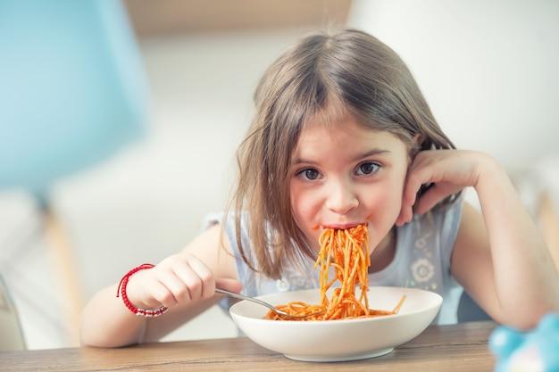 Милая маленькая девочка ребенка ест спагетти болоньезе дома.