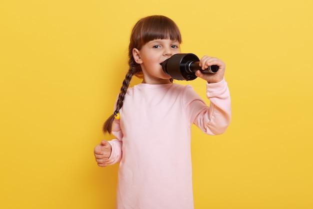 노란색 벽에 고립 된 서 귀여운 꼬마 소녀. 아이는 마이크로 노래를 부르고, 행복한 표정을 짓고, 캐주얼 한 옷차림을하고, 엔터테인먼트 공연을합니다.