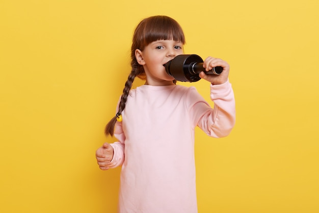 Cute little kid girl standing isolated on yellow wall. child sings song in microphone,  happy facial expression, wearing casual attire, makes performance for entertainment.