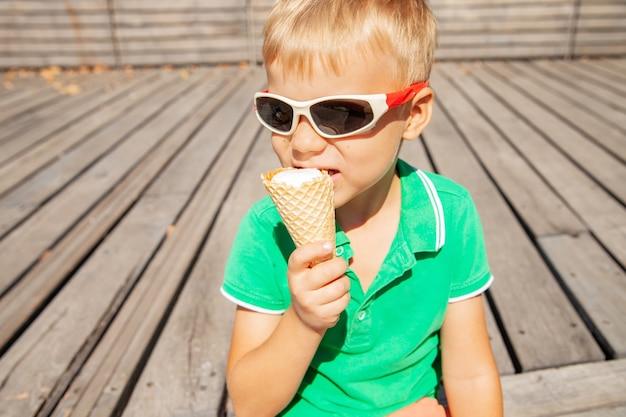 Милый маленький ребенок в солнцезащитных очках ест мороженое