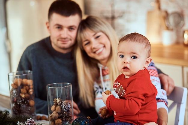 부엌에서 그의 부모와 함께 귀여운 꼬마