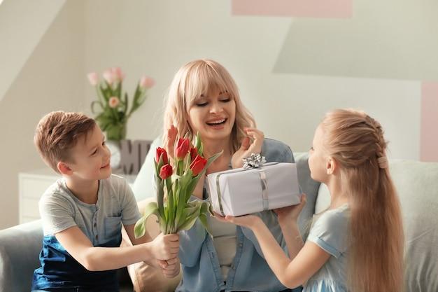 家で母親を祝福するかわいい子供たち