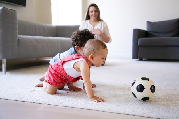 Cute little kids crawling on carpet and playing with soccer ball. caring mother sitting on floor, smiling and watching children. selective focus. family indoors, weekend and childhood concept