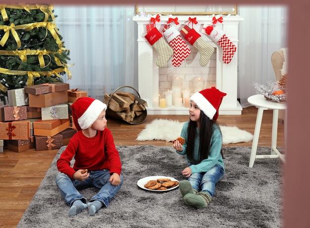 산타 모자를 쓴 귀여운 아이들이 집에서 맛있는 쿠키를 먹고 창문을 통해 봅니다.