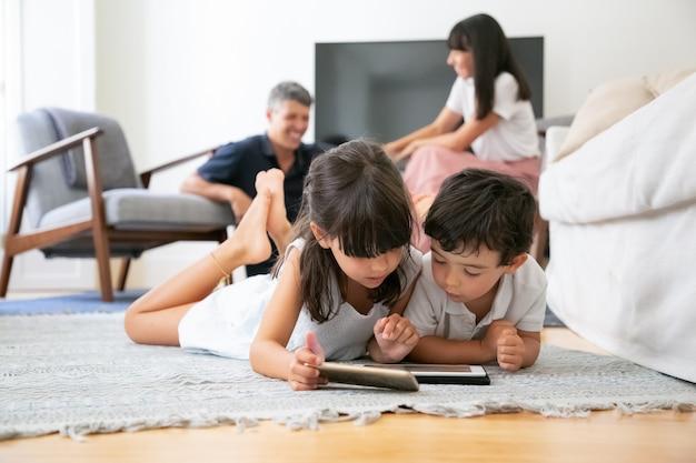 リビングルームの床に横になって、両親が笑いながら学習アプリでデジタルガジェットを使用するかわいい子供