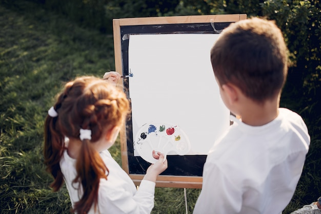 Cute little kids painting in a park