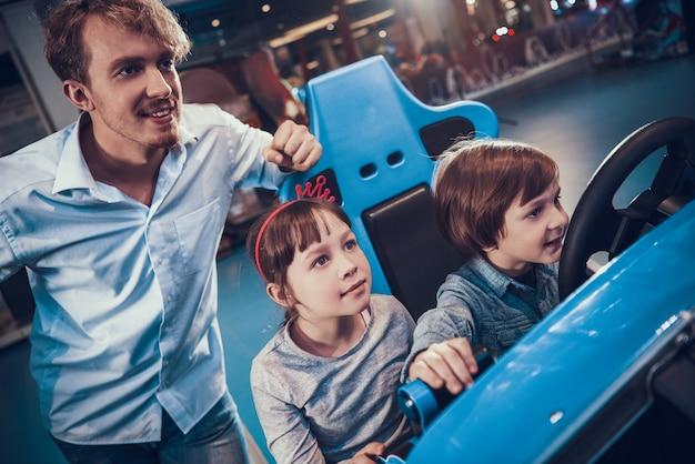 Cute little kids playing racing simulator game