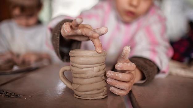 陶器のワークショップ、工芸品、粘土アートで粘土のモデリングと一緒に遊ぶかわいい子供たち