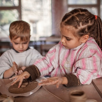 Cute little kids playing together with modeling clay in pottery workshop, craft and clay art