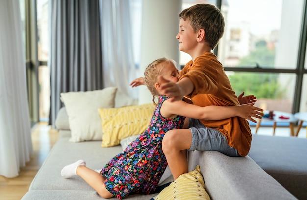 かわいい小さな子供たち、兄弟は家で抱きしめたり抱きしめたりして、愛と思いやりを示します。家族の子供たちの養育費の概念