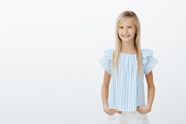 Cute little lady shopping with mom. pleased happy female child in blue blouse, holding hands on hips and smiling broadly, being amazed, having fun with friends over gray wall