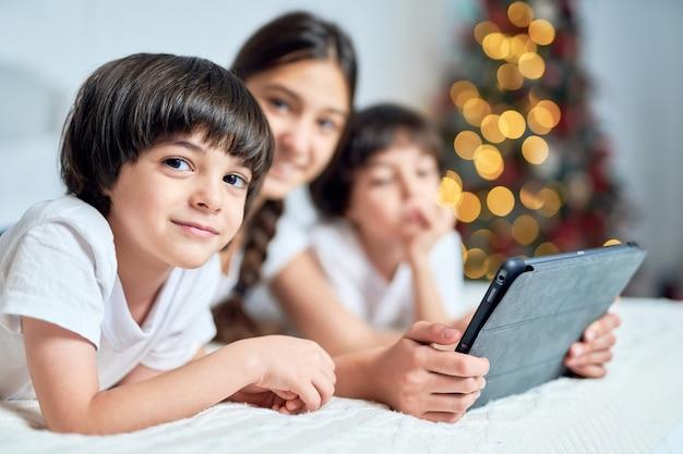 귀여운 라틴 소년이 디지털 태블릿을 사용하여 형제들과 시간을 보내는 동안 카메라를 쳐다보고 집에서 크리스마스 장식으로 꾸며진 침대에 누워 있습니다. 어린이, 기술, 겨울 방학 개념