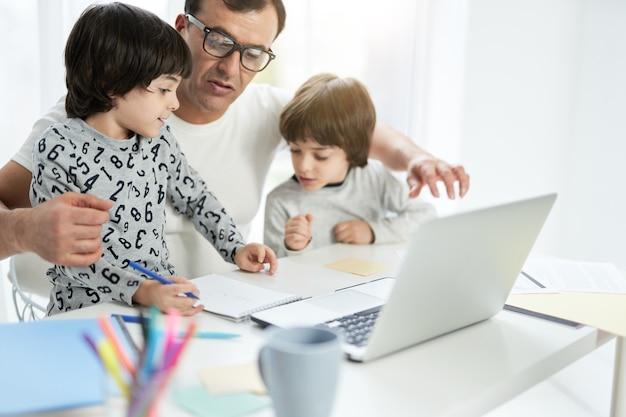 使用して自宅のビジネスマンで彼の父と弟と一緒に時間を過ごすかわいいラテン系の少年