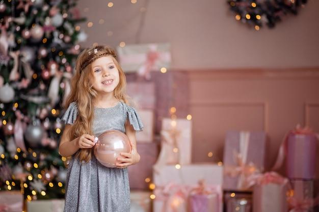 긴 머리를 가진 귀여운 웃음 금발 소녀는 배경에 크리스마스 공을 가지고 노는