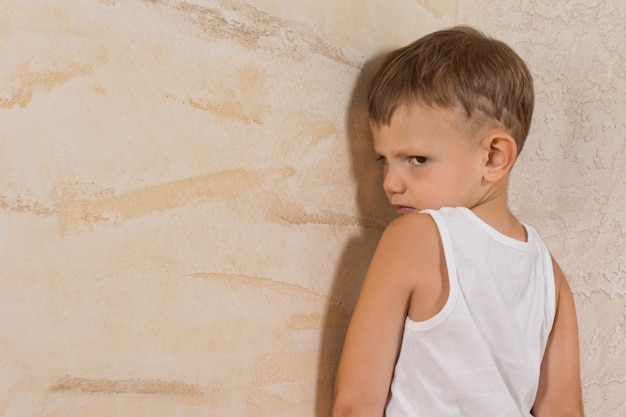 Cute little mad boy wearing white undershirt isolated on light brown walls
