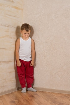 Cute little mad kid on light brown wooden walls