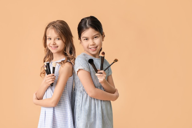 Cute little makeup artists on color background