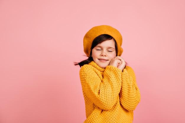 눈을 감고 포즈를 취하는 귀여운 작은 모델. 프랑스 베레모에 편안한 아이.
