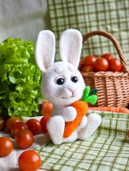 Cute little needle felted white bunny with carrot in hands on the background of vegetables