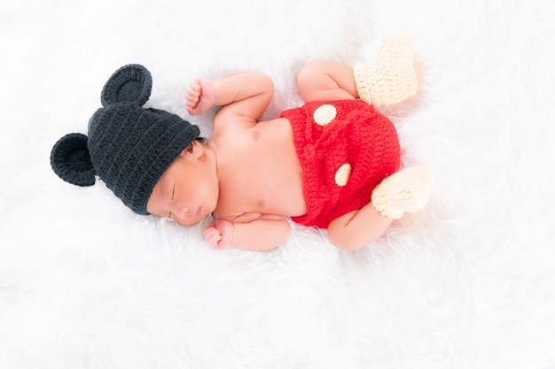 검은 모자를 쓴 귀여운 갓난아이, 귀여운 빨간 바지가 흰 침대에서 자고 있습니다. 개념 초상화 스튜디오 패션 신생아입니다.