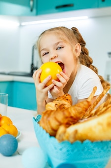 Cute little playful funny girl happily holding orange oranges, with kitchen in the background