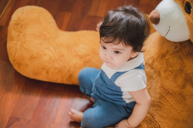 いたずらっぽく目をそらしながら、自宅でソファのサポートを受けて歩くことと立つことを学ぶかわいい小さな遊び心のある女の子の子供