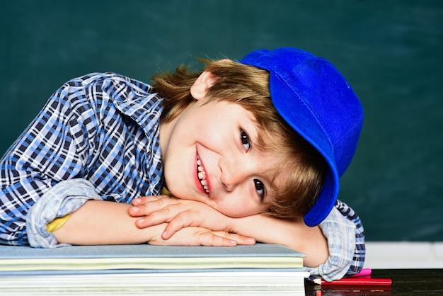Милый маленький мальчик дошкольного возраста в классе. школьник. счастливое настроение широко улыбается в школе