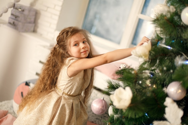 Cute little princess decorate christmas tree. holidays concept.