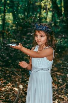 Милая маленькая принцесса девочка с голубыми бабочками в лесу. художественная обработка.