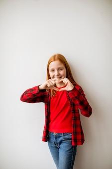 Милая маленькая рыжая девушка стоит у белой стены и показывает пальцами форму сердца