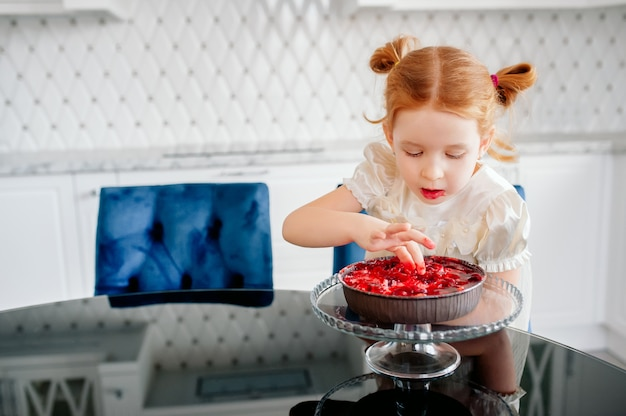 Cute little redhead baby girl eating a cake with her hands in a beautiful bright kitchen on her birthday