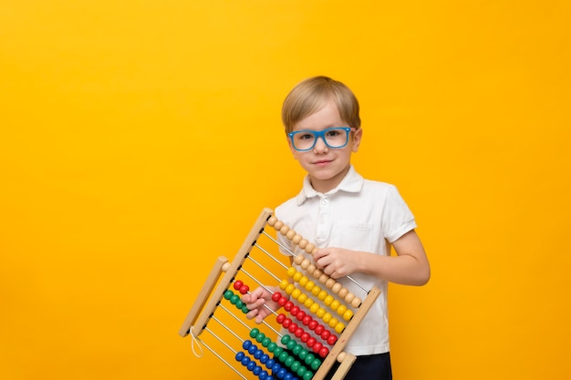 Cute little school boy in glasses holding scores, copy space. math concept