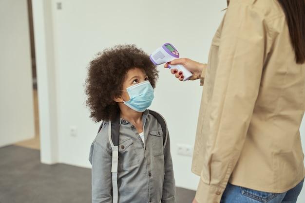 얼굴 마스크를 쓴 귀여운 작은 학교 소년이 온도 검진 아이를 측정하는 선생님을 지켜보고 있습니다.