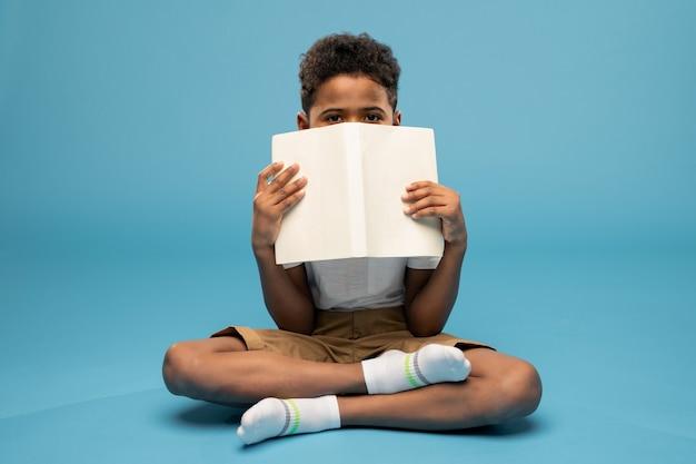 Симпатичный маленький школьник африканской национальности, держа раскрытую книгу близко к лицу и выглядывая из-за ее жульничества, сидя на полу