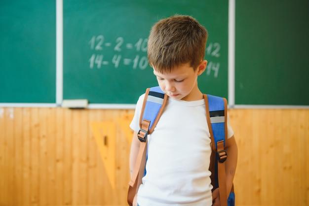Cute little schoolboy sitting in the classroom