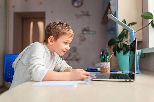 Милый маленький школьник учится дома, делая домашнее задание