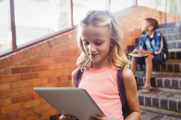 Cute little schoolgirl looking at her digital tablet