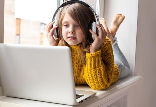 自宅でノートパソコンを使用しているかわいい女子高生はインターネット上で通信します