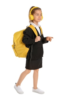 Милая маленькая школьница с наушниками на белом